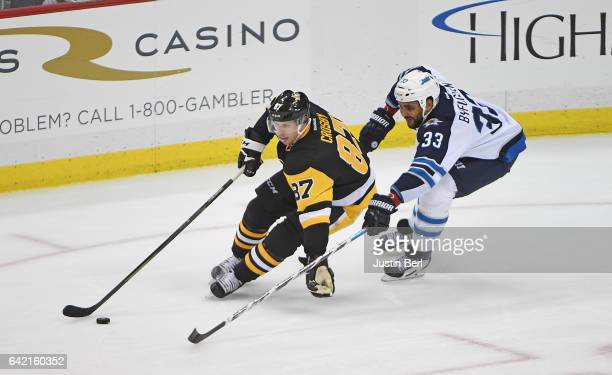 Sidney Crosby of the Pittsburgh Penguins handles the puck as Dustin Byfuglien of the Winnipeg Jets defends in the third period during the game at PPG...