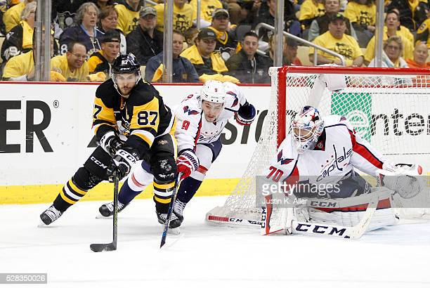 Sidney Crosby of the Pittsburgh Penguins handles the puck in front of Dmitry Orlov of the Washington Capitals in Game Four of the Eastern Conference...
