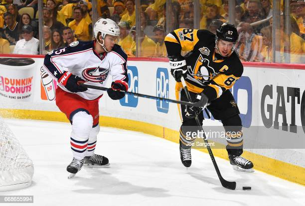 Sidney Crosby of the Pittsburgh Penguins handles the puck in front of William Karlsson of the Columbus Blue Jackets in Game Two of the Eastern...