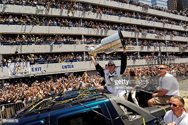 Sidney Crosby of the Pittsburgh Penguins holds the Stanley Cup aloft for the fans along the Blvd of the Allies during the Stanley Cup Champion...