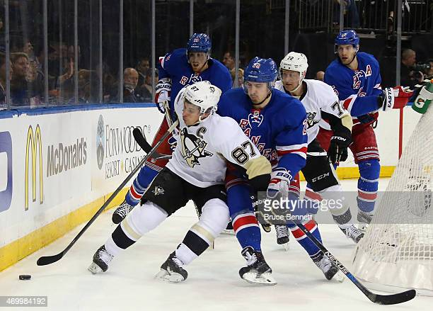 Sidney Crosby of the Pittsburgh Penguins is checked by Chris Kreider of the New York Rangers during the first period in Game One of the Eastern...