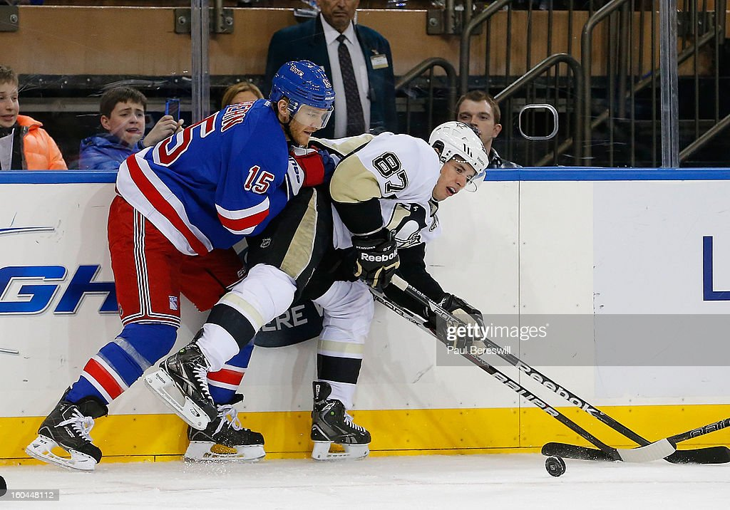 Sidney Crosby #87 of the Pittsburgh Penguins is checked by Jeff Halpern #15 of the New York Rangers in the third period of an NHL hockey game at Madison Square Garden on January 31, 2013 in New York City.