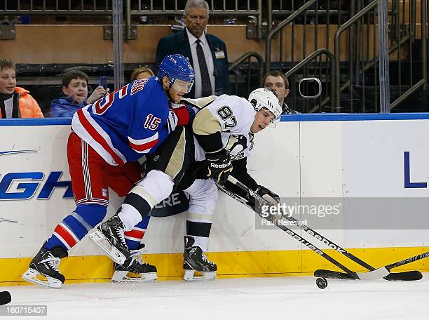 Sidney Crosby of the Pittsburgh Penguins is checked by Jeff Halpern of the New York Rangers during an NHL hockey game at Madison Square Garden on...