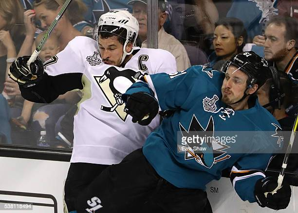 Sidney Crosby of the Pittsburgh Penguins is checked by Justin Braun of the San Jose Sharks during the first period in Game Three of the 2016 NHL...
