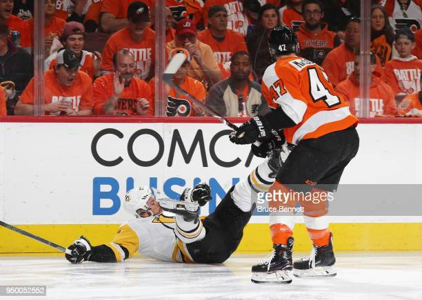 Sidney Crosby of the Pittsburgh Penguins is tripped up by Andrew MacDonald of the Philadelphia Flyers during the first period in Game Six of the...