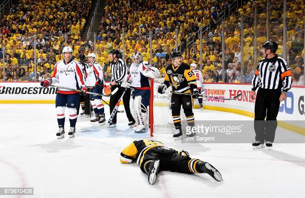 Sidney Crosby of the Pittsburgh Penguins lays on the ice injured after being cross checked in the head during the first period against the Washington...