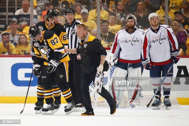 Sidney Crosby of the Pittsburgh Penguins leaves the ice with trainer Chris Stewart after taking a hit in the first period while playing the...
