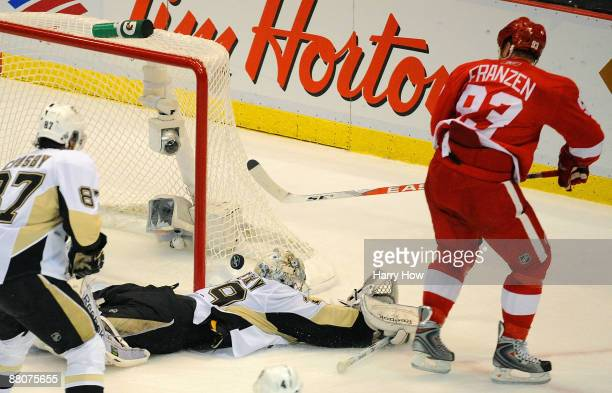Sidney Crosby of the Pittsburgh Penguins looks on as Johan Franzen of the Detroit Red Wings scores a goal past goaltender MarcAndre Fleury during...