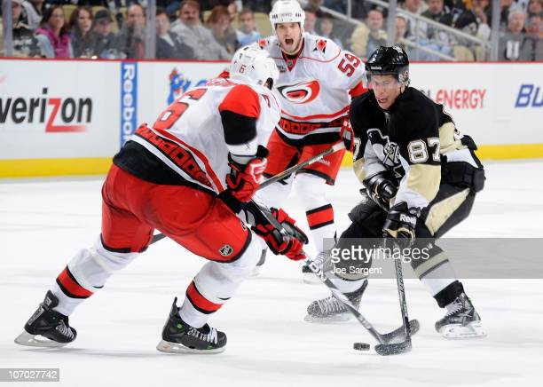 Sidney Crosby of the Pittsburgh Penguins moves the puck between the defense of Tim Gleason and Chad Larose of the Carolina Hurricanes on November 19...