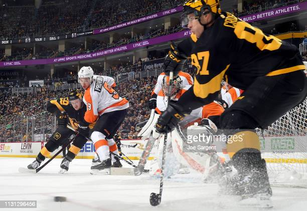 Sidney Crosby of the Pittsburgh Penguins moves the puck in front of Carter Hart of the Philadelphia Flyers at PPG Paints Arena on March 17 2019 in...