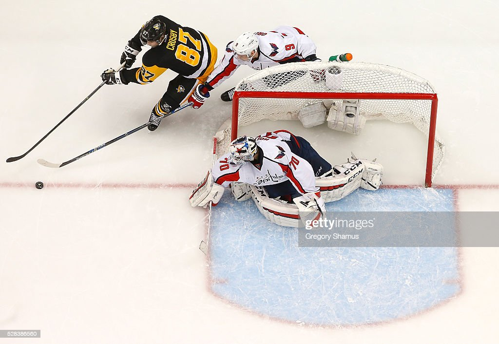 Sidney Crosby #87 of the Pittsburgh Penguins moves the puck in front of Dmitry Orlov #9 and Braden Holtby #70 of the Washington Capitals in Game Four of the Eastern Conference Second Round during the 2016 NHL Stanley Cup Playoffs at Consol Energy Center on May 2, 2016 in Pittsburgh, Pennsylvania.
