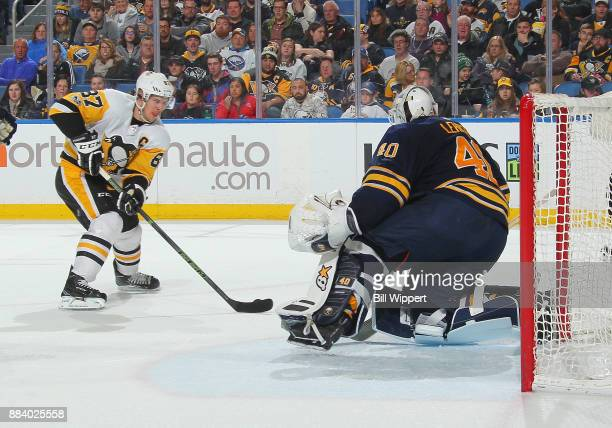 Sidney Crosby of the Pittsburgh Penguins moves with the puck in front of Robin Lehner of the Buffalo Sabres during the second period of an NHL game...