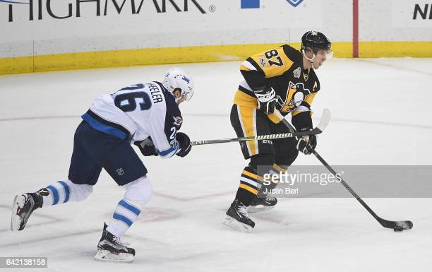 Sidney Crosby of the Pittsburgh Penguins passes the puck to Chris Kunitz for Crosby's 1000th career point in the first period during the game against...