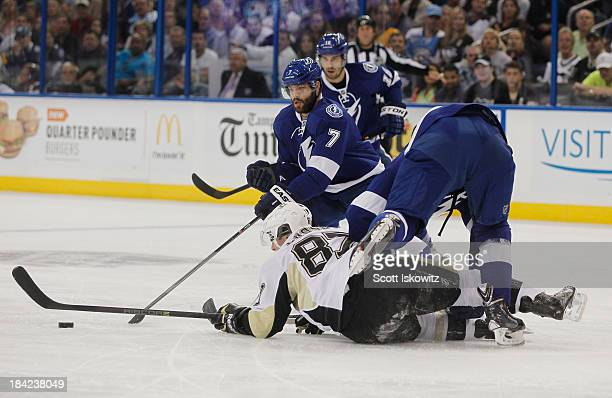 Sidney Crosby of the Pittsburgh Penguins passes the puck while on the ice against Radko Gudas and Matt Carle of the Tampa Bay Lightning during the...