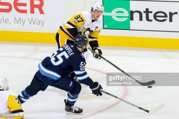 Sidney Crosby of the Pittsburgh Penguins plays the puck as Mark Scheifele of the Winnipeg Jets defends during second period action at the Bell MTS...