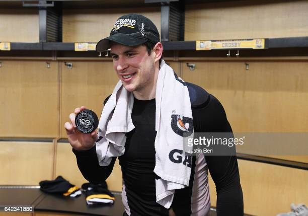 Sidney Crosby of the Pittsburgh Penguins poses with the puck he scored his 1000th career point with after the Pittsburgh Penguins 43 win over the...