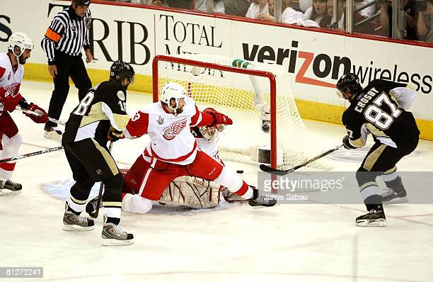 Sidney Crosby of the Pittsburgh Penguins scores his second goal over goaltender Chris Osgood and Brad Stuart of the Detroit Red Wings during the...