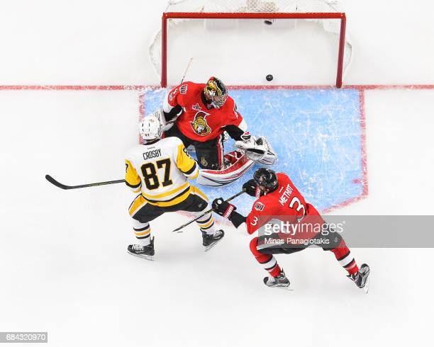 Sidney Crosby of the Pittsburgh Penguins scores on goaltender Craig Anderson as teammate Marc Methot of the Ottawa Senators tries to defend during...