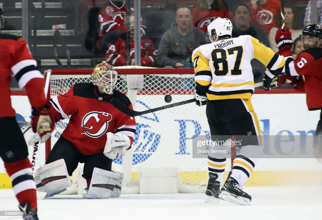 Sidney Crosby #87 of the Pittsburgh Penguins scores the game winning goal in overtime against Keith Kinkaid #1 of the New Jersey Devils at the Prudential Center on March 29, 2018 in Newark, New Jersey. The Penguins defeated the Devils 4-3 in overtime.