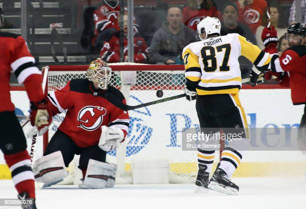 Sidney Crosby of the Pittsburgh Penguins scores the game winning goal in overtime against Keith Kinkaid of the New Jersey Devils at the Prudential...