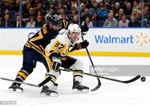 Sidney Crosby of the Pittsburgh Penguins scores with one hand on a breakaway as Zach Bogosian of the Buffalo Sabres tries to defend during the first...