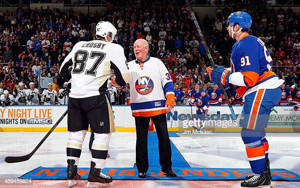 Sidney Crosby of the Pittsburgh Penguins shakes hands with former New York Islander Billy Smith as John Tavares of the New York Islanders looks on...