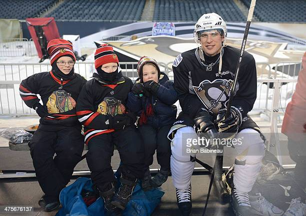 Sidney Crosby of the Pittsburgh Penguins sits with young Chicago Blackhawks fans behind the bench area during the 2014 NHL Stadium Series practice...