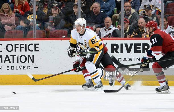 Sidney Crosby of the Pittsburgh Penguins skates for a loose puck ahead of Derek Stepan of the Arizona Coyotes during the second period at Gila River...