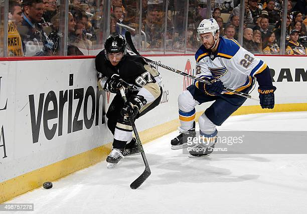 Sidney Crosby of the Pittsburgh Penguins skates for the loose puck alongside Kevin Shattenkirk of the St Louis Blues at Consol Energy Center on...