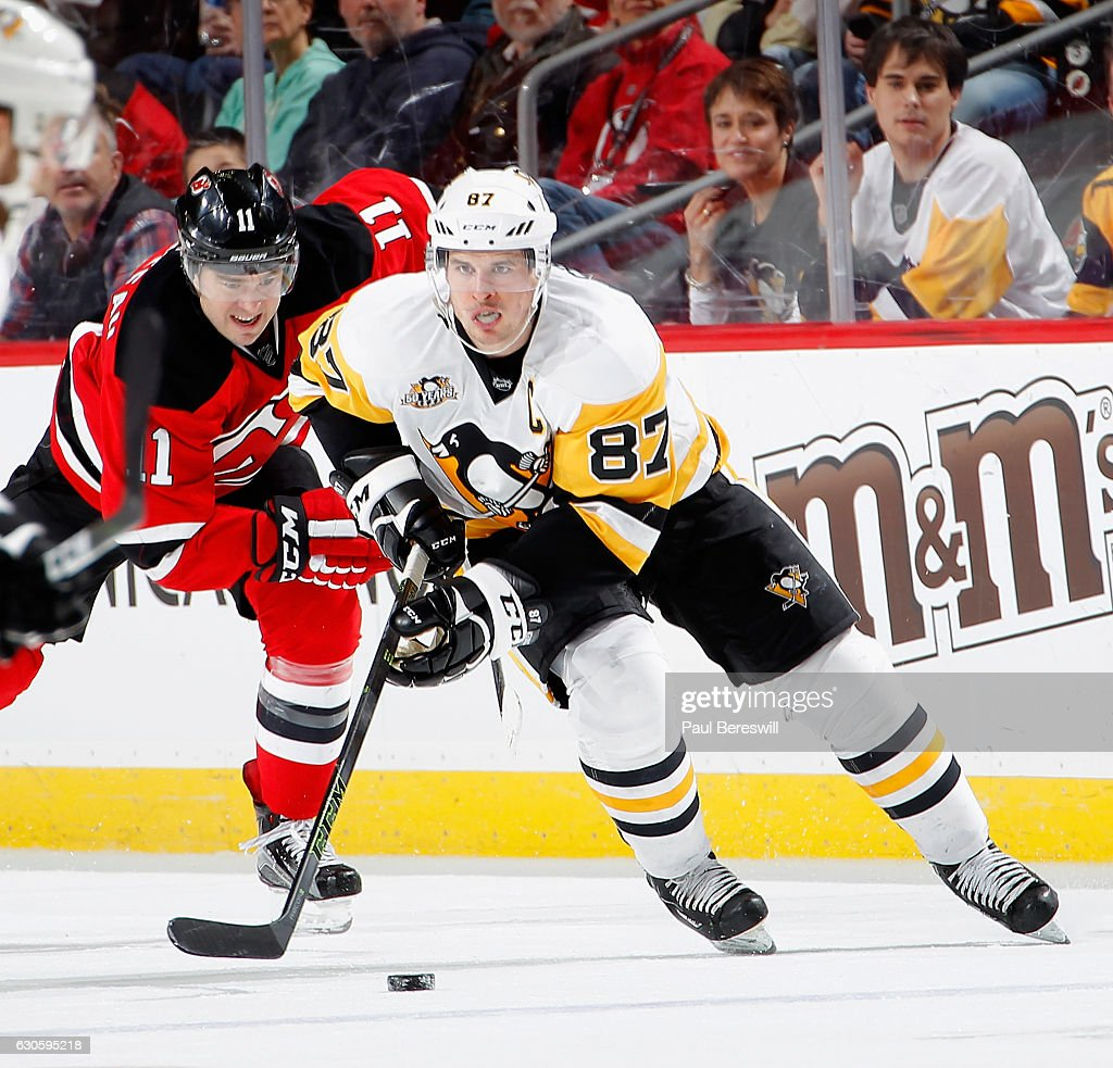 Sidney Crosby #87 of the Pittsburgh Penguins skates into the Devils zone with the puck as PA Parenteau #11 of the New Jersey Devils gives chase in the third period of an NHL hockey game at Prudential Center on December 27, 2016 in Newark, New Jersey. Penguins won 5-2.