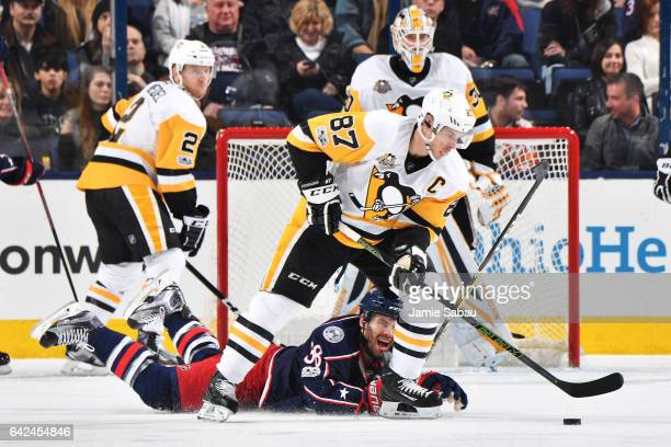 Sidney Crosby of the Pittsburgh Penguins skates the puck away from Boone Jenner of the Columbus Blue Jackets as he falls to the ice during the second...