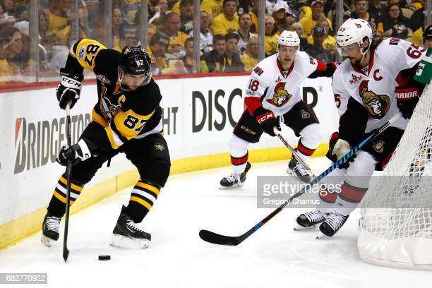 Sidney Crosby of the Pittsburgh Penguins skates with the puck against Erik Karlsson of the Ottawa Senators during the second period in Game One of...
