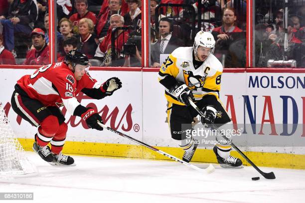 Sidney Crosby of the Pittsburgh Penguins skates with the puck against Ryan Dzingel of the Ottawa Senators in Game Three of the Eastern Conference...
