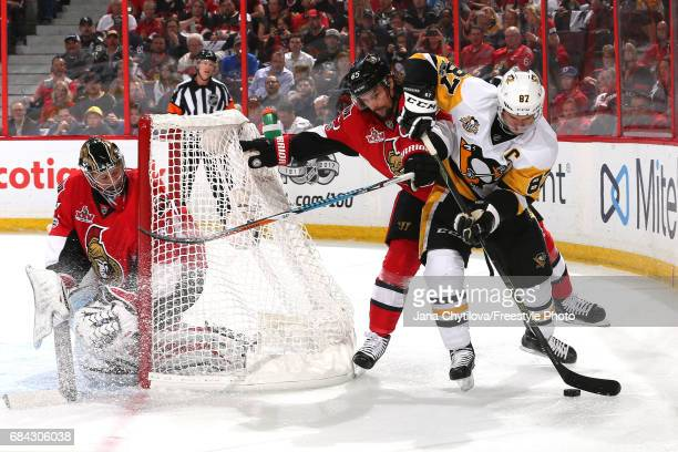 Sidney Crosby of the Pittsburgh Penguins skates with the puck behind the net against Erik Karlsson of the Ottawa Senators during the first period in...