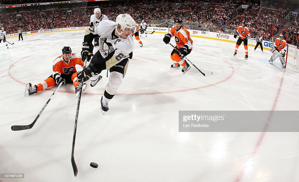 Sidney Crosby #87 of the Pittsburgh Penguins skates with the puck in the corner against the defense of Darroll Powe #36(L) and Kimmo Timonen #44(R) of the Philadelphia Flyers on December 14, 2010 at the Wells Fargo Center in Philadelphia, Pennsylvania.