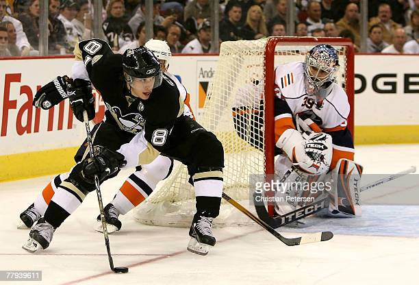 Sidney Crosby of the Pittsburgh Penguins skates with the puck past goaltender Rick DiPietro of the New York Islanders during the second period of the...