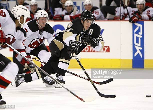 Sidney Crosby of the Pittsburgh Penguins splits the defense by Johnny Oduya and Paul Martin New Jersey Devils on October 17 2007 at Mellon Arena in...