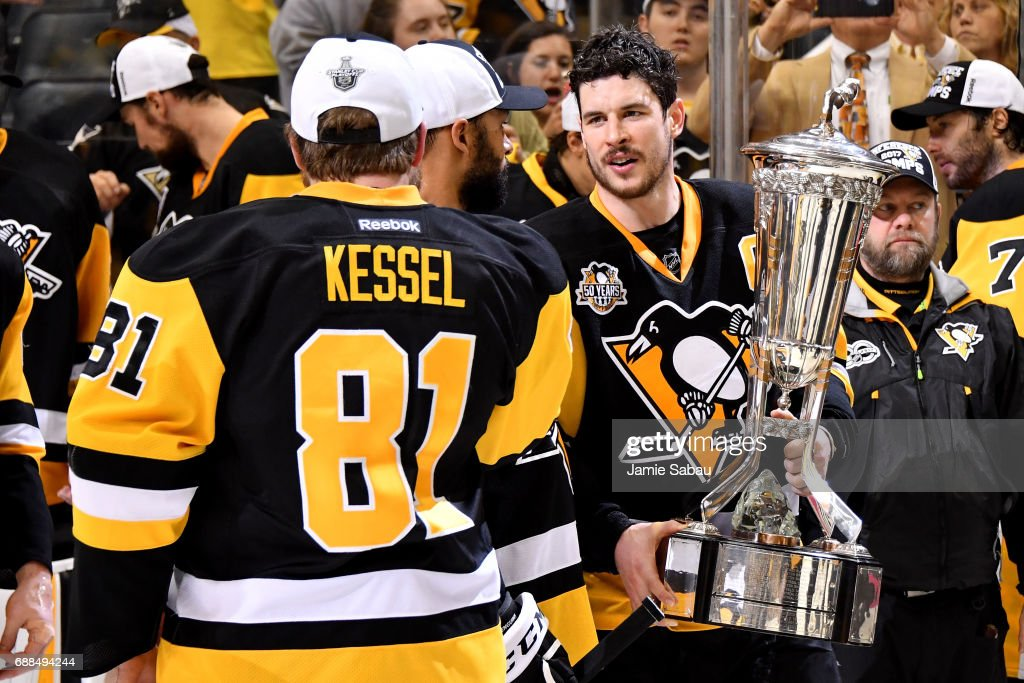 Sidney Crosby #87 of the Pittsburgh Penguins talks with Phil Kessel #81 as he holds the Prince of Wales Trophy after winning Game Seven of the Eastern Conference Final against the Ottawa Senators during the 2017 NHL Stanley Cup Playoffs at PPG PAINTS Arena on May 25, 2017 in Pittsburgh, Pennsylvania. The Pittsburgh Penguins defeated the Ottawa Senators with a score of 3 to 2.