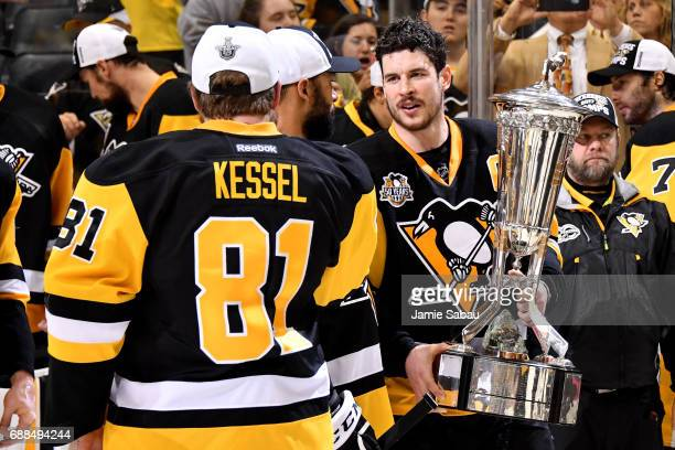 Sidney Crosby of the Pittsburgh Penguins talks with Phil Kessel as he holds the Prince of Wales Trophy after winning Game Seven of the Eastern...