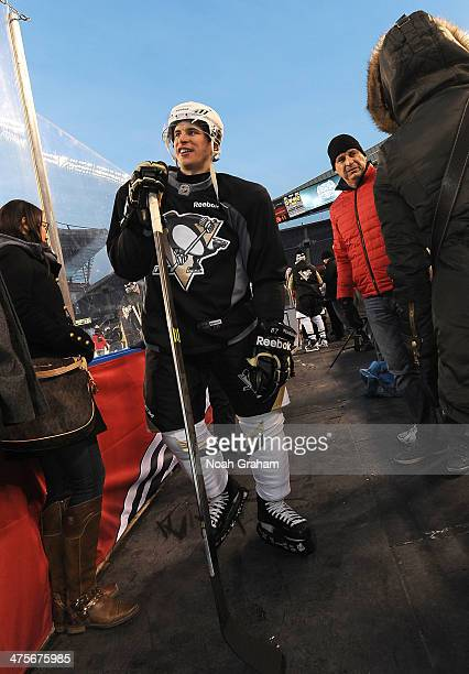 Sidney Crosby of the Pittsburgh Penguins walks along the side boards off the ice as father Troy looks on during the 2014 NHL Stadium Series family...