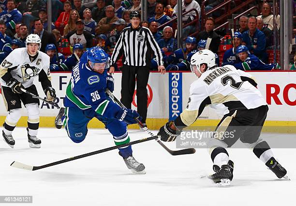 Sidney Crosby of the Pittsburgh Penguins watches as Jannik Hansen of the Vancouver Canucks takes a shot past Matt Niskanen of the Penguins during...