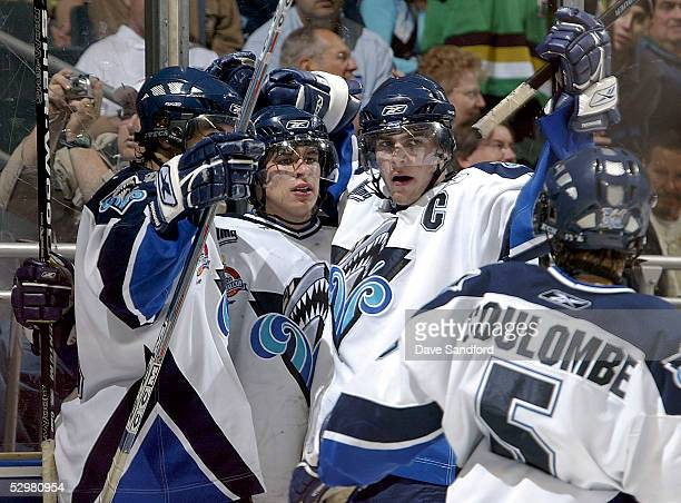 Sidney Crosby of the Rimouski Oceanic celebrates with teammates MarcAntoine Pouliot and Patrick Coulombe after scoring on the Kelowna Rockets during...