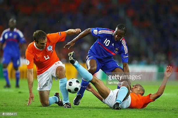 Sidney Govou of France is challenged by Joris Mathijsen and Nigel de Jong of Netherlands during the UEFA EURO 2008 Group C match between Netherlands...