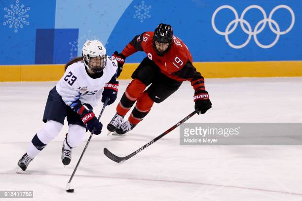 Sidney Morin of the United States handles the puck against Brianne Jenner of Canada during the Women's Ice Hockey Preliminary Round Group A game on...