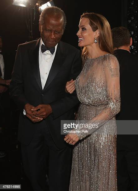 Sidney Poitier and Angelina Jolie speak backstage during the Oscars held at Dolby Theatre on March 2 2014 in Hollywood California