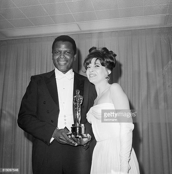 Sidney Poitier receives an Oscar presented by Anne Bancroft in Santa Monica California on April 13 1964 He won Best Performance by an Actor for his...