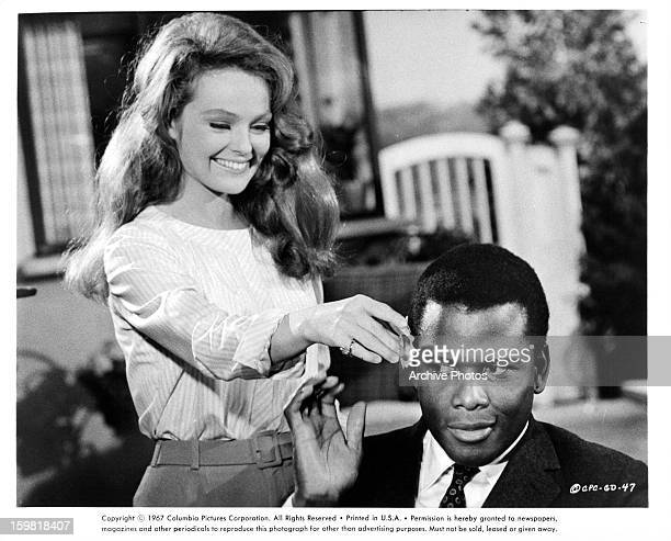 Sidney Poitier shooing away Katharine Houghton as she tries to attach a flower to his ear in a scene from the film 'Guess Who's Coming to Dinner' 1967