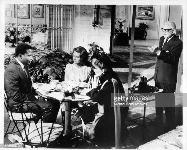 Sidney Poitier sitting at a table with Katharine Hepburn and Katharine Houghton as Spencer Tracey stands in the background speaking in a scene from...