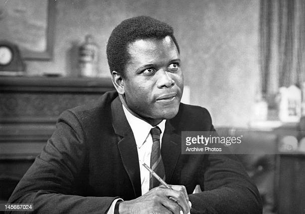 Sidney Poitier sitting with pencil while looking up in a scene from the film 'To Sir With Love' 1967