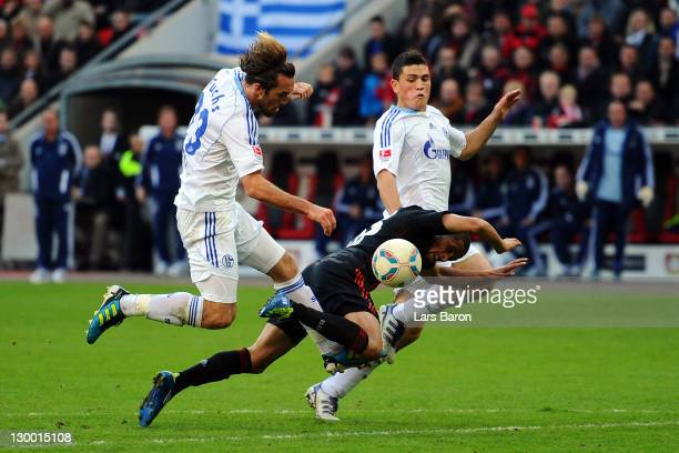 Sidney Sam of Leverkusen is challenged by Christian Fuchs and Kyriakos Papadopoulos of Schalke during the Bundesliga match between Bayer 04...